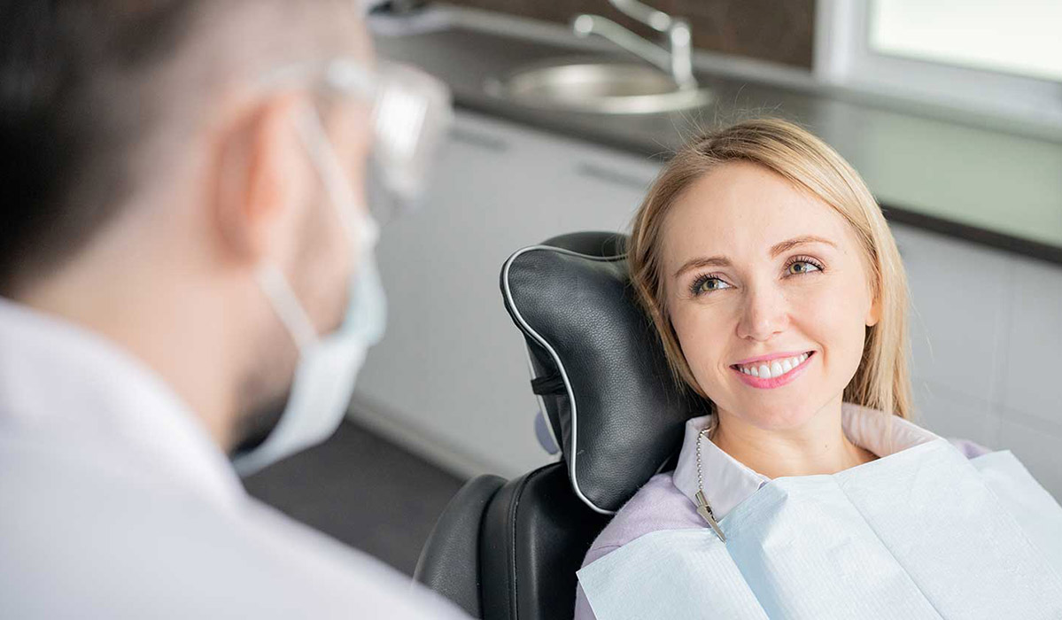 Woman in dentist chair smiling at the dentist